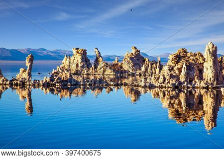 Magic sunrise on the lake. Mono Lake  in California. Lime-tuff towers of bizarre shapes rise from the bottom of the lake. Magnificent reflections of tuff outliers in lake water.