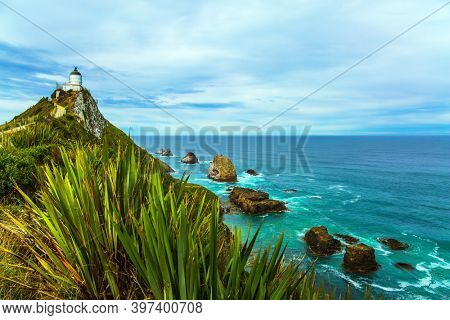 South Island, New Zealand. The white building of the lighthouse looks spectacular on a high cape. Nugget Point Lighthouse on the Cape Nugget. The concept of active, environmental and photo tourism