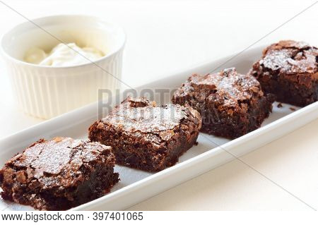 A Row Of Chocolate Brownies On An Oblong Ceramic Plate Served With Whipped Cream.