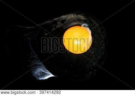 Beaten Chicken Egg On A Black Background. Flowing Egg White And Solid Egg Yolk.