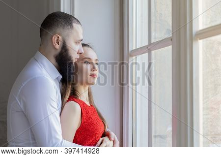 Sad Young Couple Looking In The Window On Sunny Day. Man And Woman Hugging At Home After A Quarrel,