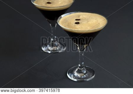 Espresso Martini Cocktail Garnished With Coffee Beans On Dark Table. Two Martini Glasses On A Black