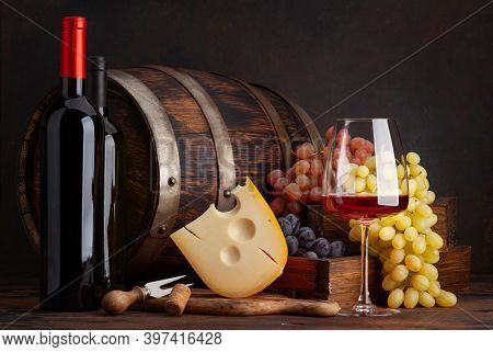 Wine bottles, grapes, cheese, glass of red wine and old wooden barrel. With copy space
