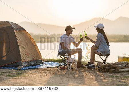 Young adult Asian couple drinking beer beside their tent campsite while sunset. Camping trip with dog outdoor activity campsite concept.