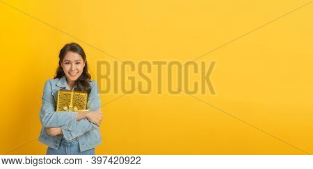 Wide Banner. Happy Asian Pretty Woman In Casual Clothing Jeans Smiling And Hold New Year Gift Box Ov