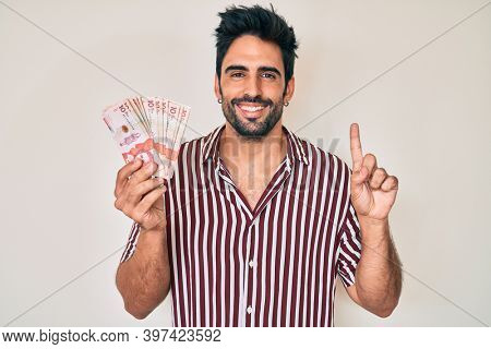Handsome hispanic man with beard holding colombian pesos smiling with an idea or question pointing finger with happy face, number one