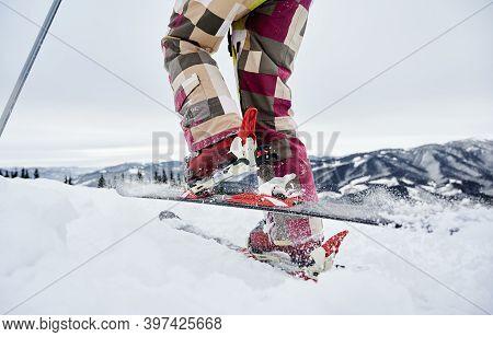 Close-up Cropped Snapshot Of Skiers Legs, Ski Fastening And Skis, Making Step Forward, Ski Tour. Low