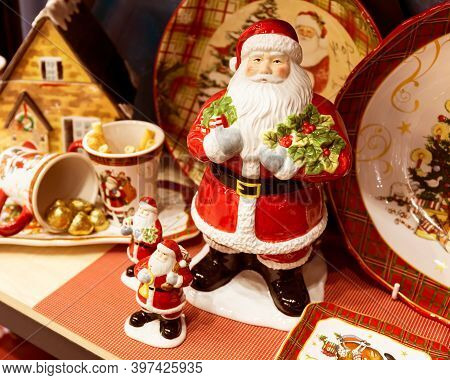 Big Toy Santa Claus And Two Smaller Santa Claus On The Background Of Beautiful Christmas Decorations