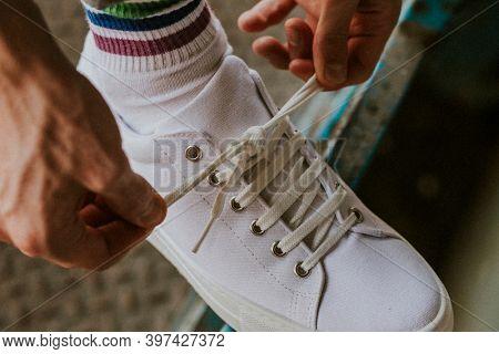 Man tying shoelaces on canvas sneaker