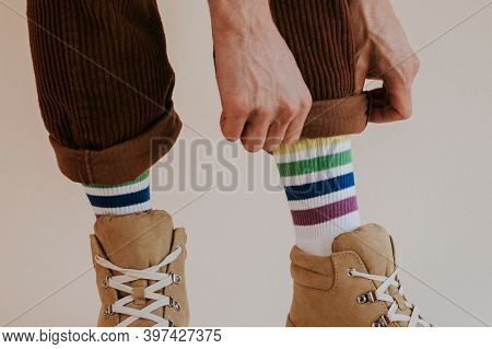 Man folding up pant leg with sneaker