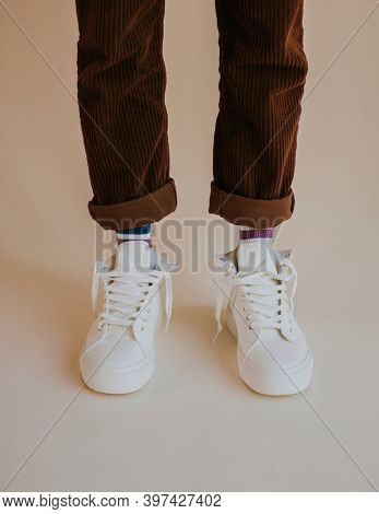 White sneakers with untied laces on man model