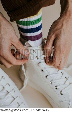 Model tying shoelaces white sneaker