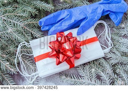 Pack Of Medical Face Masks As Gift With Red Ribbon And Protective Gloves On The Background Of Spruce