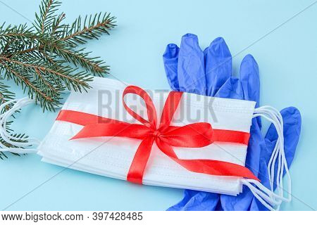 Pack Of Medical Face Masks As Gift With Red Ribbon And Protective Gloves On Light Blue Background Wi