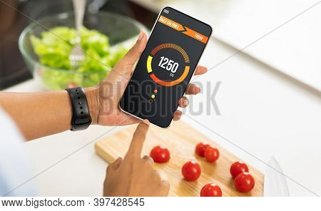 Weightloss Concept. Unrecognizable Woman Holding Smartphone With Opened App For Counting Daily Calor