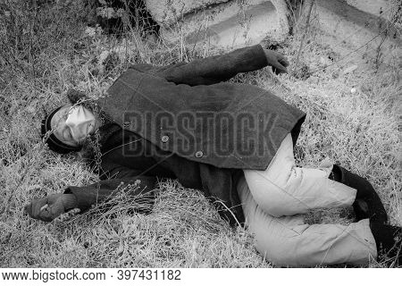 A Homeless Man In A Medical Mask Lies Unconscious On The Wet Ground. The Poor Dirty Man Lies Dead On