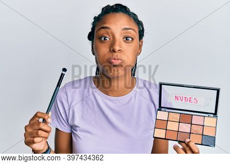 African american woman holding blush palette of nudes colors puffing cheeks with funny face. mouth inflated with air, catching air.