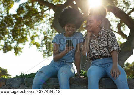 Front view close up of two young smiling adult mixed race sisters sitting on a wall in an urban park, using a smartphone and sharing earphones to listen to music, backlit with lens flare