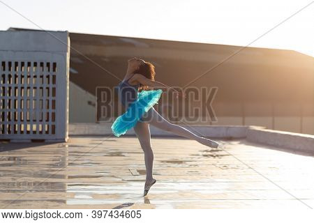 Side view of a young mixed race female ballet dancer wearing a blue tutu standing on one leg on her toes in a ballet pose, on the rooftop of an urban building, backlit by sunlight