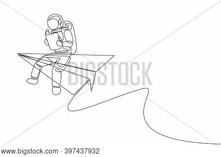 One Continuous Line Drawing Of Young Astronaut Sitting On The Edge Of Flying Paper Plane While Readi