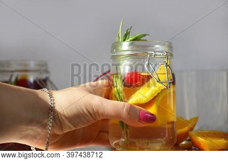 Female Hand Holds Detox Water With Orange, Cranberry And Rosemary, Healthy Drink For The Diet, Vitam