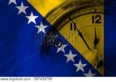 Bosnia And Herzegovina, Bosnian, Herzegovinian Flag With Clock Close To Midnight In The Background.