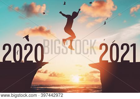 Silhouette Man Jumping Between Cliff With Number 2020 To 2021 At Tropical Sunset Beach. Freedom Chal