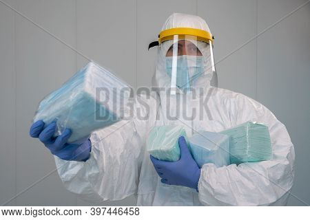 Male Nurse Wears Protective Suit Shows A Pack Of Medical Masks. Coronavirus