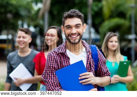 Handsome Spanish Male Student With Group Of Other Students Outdoor In Summer In City