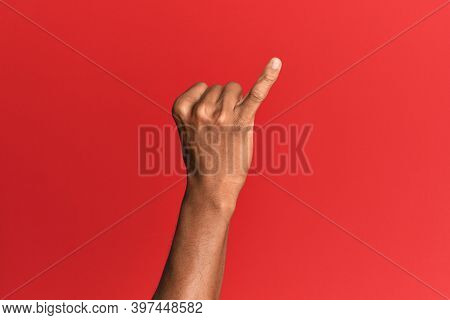 Hand of hispanic man over red isolated background showing little finger as pinky promise commitment, number one