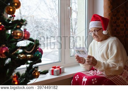 Elderly Caucasian Woman Santa Hat Sits By Window With Glasses Her Face And Reads Greeting Card.chris