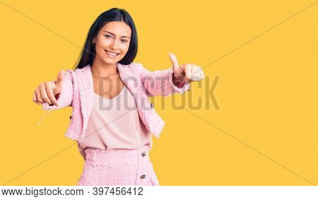 Young beautiful latin girl wearing business clothes approving doing positive gesture with hand, thumbs up smiling and happy for success. winner gesture.