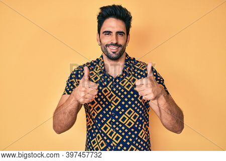 Handsome hispanic man with beard wearing 80s disco style shirt success sign doing positive gesture with hand, thumbs up smiling and happy. cheerful expression and winner gesture.