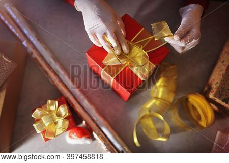 A Girl In A Santa\'s Helper Hat And A Respiratory Protection Mask And Gloves Is Packing Gifts On Chr