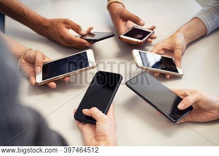 Close up of guys and girls hands in circle using smart phone. High angle view of multiple hands holding mobile phone with empty screen. Group of multi cultural friends using smartphone together.