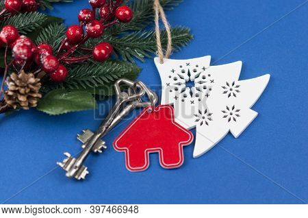 Beautiful Christmas background: decorative house and key to the lock. Concept of finance and housing loans. Top view. Real estate.