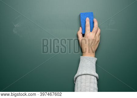Woman's Hand Wipes A Green Chalk Board With A Blue Sponge, Close Up