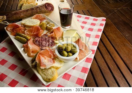 Homelike appetizer with salami, bread, olives, cheese, ham, pickles and red wine