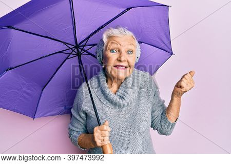 Senior grey-haired woman holding purple umbrella screaming proud, celebrating victory and success very excited with raised arm