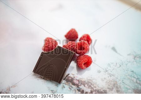 Bitten Chocolate Bar And Raspberries On A Colorful Placemat