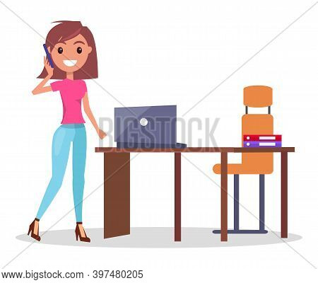 Businesswoman Talking By Phone Standing Near Office Table With Laptop And Armchair, Smiling Pretty W