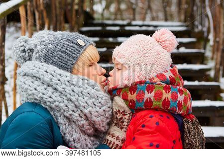 Happy Mother Kissing Baby Girl On The Walk In Winter Snowy Park.