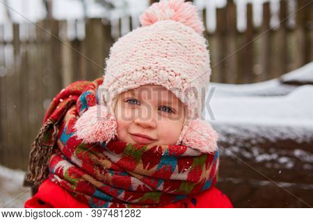 Winter Outdoor Portrait Of Adorable Dreamy Baby Girl In Knitted Hat And Scarf.