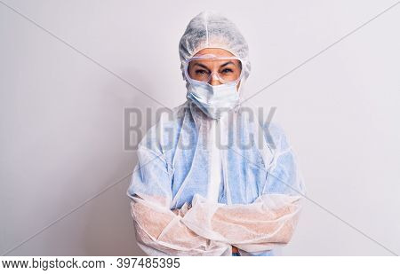 Middle age nurse woman wearing protection coronavirus equipment over white background skeptic and nervous, disapproving expression on face with crossed arms. Negative person.