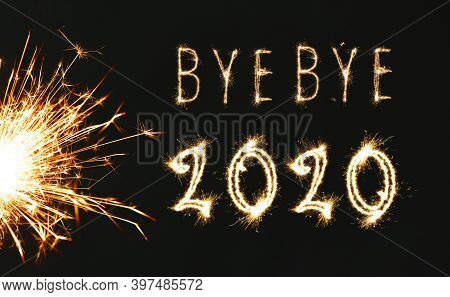 Bye Bye 2020. Bright Text And Sparkler On Black Background