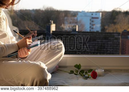A Young Girl Sits On The Windowsill And Writes Something In A Notebook, In The Morning
