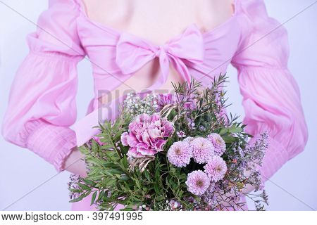 A Bouquet Of Festive Flowers And A Girl In A Pink Dress Stands With Her Back