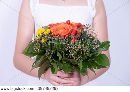 A Girl In A White Dress Holds A Spring Festive Bouquet Of Flowers In Her Hands