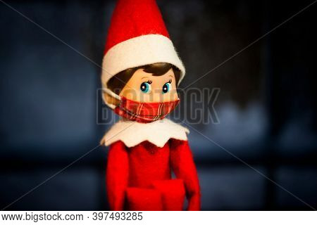Christmas Elf on the Shelf with a covid quarantine mask, social distancing during the holidays concept