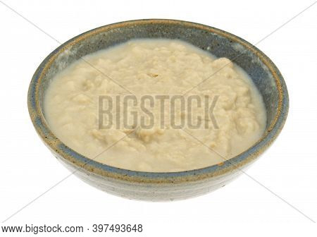 Side View Of A Bowl Of Rice Cereal For Infants In A Stoneware Bowl With Water Added Isolated On A Wh